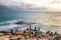 Fishermen on the coastline at dawn, Arniston, Western Cape, South Africa
