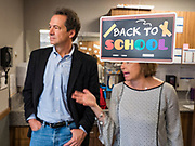 "12 SEPTEMBER 2019 - DES MOINES, IOWA: Governor STEVE BULLOCK (D-MT), left, talks to JEANNINE LAUGHLIN, Area Administrator for New Horizons Academy in front of a ""back to school"" sign after a Caucus for Kids Facebook Live broadcast sponsored by the Children's Policy Coalition at the school. Gov. Bullock is vying to be the Democratic party's nominee in 2020. He is campaigning in Iowa this week he didn't qualify for the September 12 debate. Iowa traditionally hosts the the first election event of the presidential selection cycle. The Iowa Caucuses will be on Feb. 3, 2020.                  PHOTO BY JACK KURTZ"
