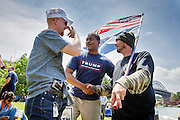 Sean Bosilivic (r) and Josh Glaspie (l) in the Michigan chapter of the right wing US Militia talks with pro gun supporter Eric Smith (center). The Republican National Convention in Cleveland, where Donald Trump is nominated as the republican presidential candidate.