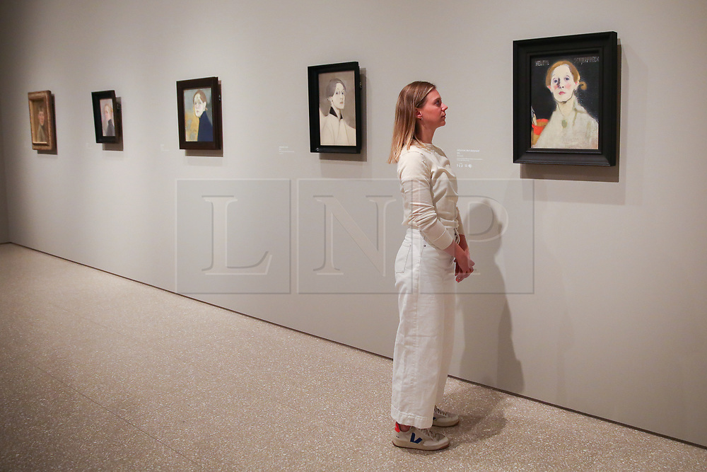 """© Licensed to London News Pictures. 17/07/2019. London, UK. A staff member views Helene Schjerfbeck's painting """"Self-portrait, Black Background 1915"""" at Royal Academy of Arts during the preview of her first ever exhibition in the UK. The exhibition features around 65 portraits, landscapes and still life, charting the development of Helene Schjerfbeck's work from a naturalistic style inspired by French Salon painters in the early 1880s, to a radically abstracted and modern approach from the turn of the twentieth century onwards. The exhibition runs  from 20 July to 27 October 2019. Photo credit: Dinendra Haria/LNP"""