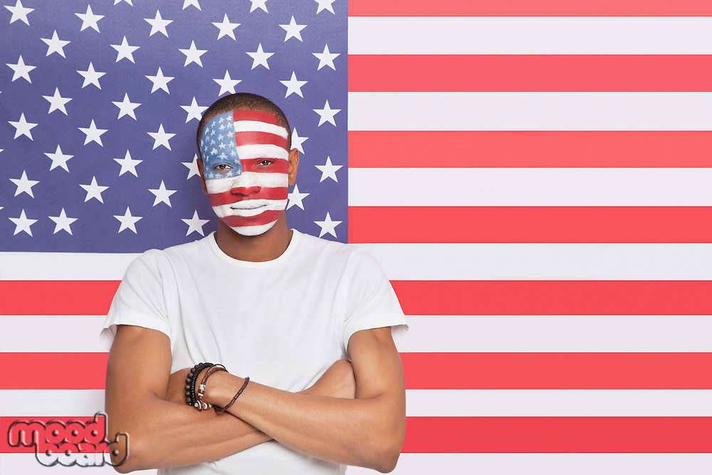 Portrait of confident Young man with painted face against American flag