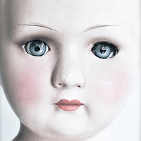 Close up of female dolls face with blue eyes and lipstick