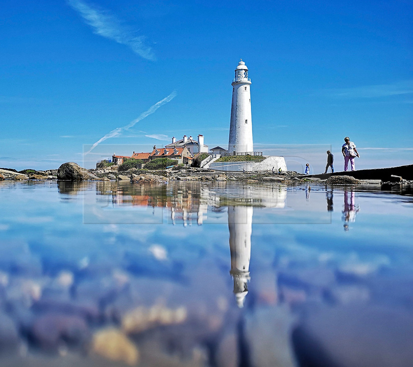 © Licensed to London News Pictures. 20/05/2019. Whitley Bay, UK. St. Mary's Lighthouse at Whitley Bay in North Tynemouth, reflected in the sea on a clear and sunny day on the north east coast. Photo credit: Colin Scarr/LNP