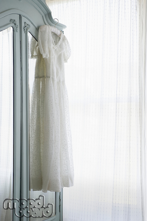 Christening gown on wardrobe at window with net curtains