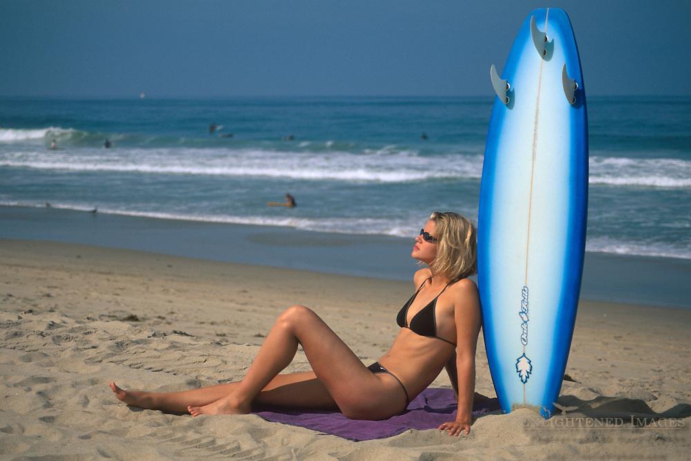 Beautiful young woman in bikini resting against surfboard in sand, Manhattan Beach, Los Angeles County, California