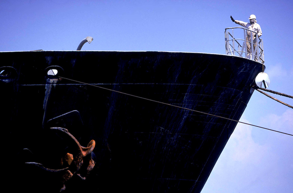 A dock worker dressed in white overalls signals from the tankers bow. His figure contrasted against the ship illustrates the scale of the tanker..The harbour is being developed by South Asia Gateway Terminals (Pvt) Ltd.