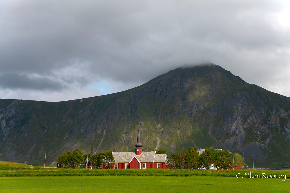 Flagstad Church next to a rocky mountain.  Flagstad, Lofoten Islands, Norway