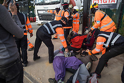 Harefield, UK. 12th September, 2020. Security guards working on behalf of HS2 forcibly restrain environmental activists acting in solidarity with HS2 Rebellion from the road in front of a gate providing access to a site for the HS2 high-speed rail link. Anti-HS2 activists continue to try to prevent or delay works on the controversial £106bn HS2 high-speed rail link in the Colne Valley where thousands of trees have already been felled.