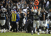 Oakland Raiders middle linebacker Miles Burris (56) joins players and coaches on the sideline cheering as the Raiders win their first game of the season during the NFL week 12 regular season football game against the Kansas City Chiefs on Thursday, Nov. 20, 2014 in Oakland, Calif. The Raiders won their first game of the season 24-20. ©Paul Anthony Spinelli
