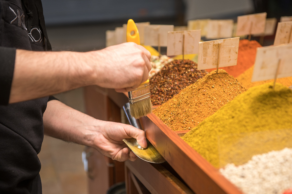 Male merchant uses paint brush to tidy up excess spices off of side of container at Istanbul Spice bazaar in Turkey