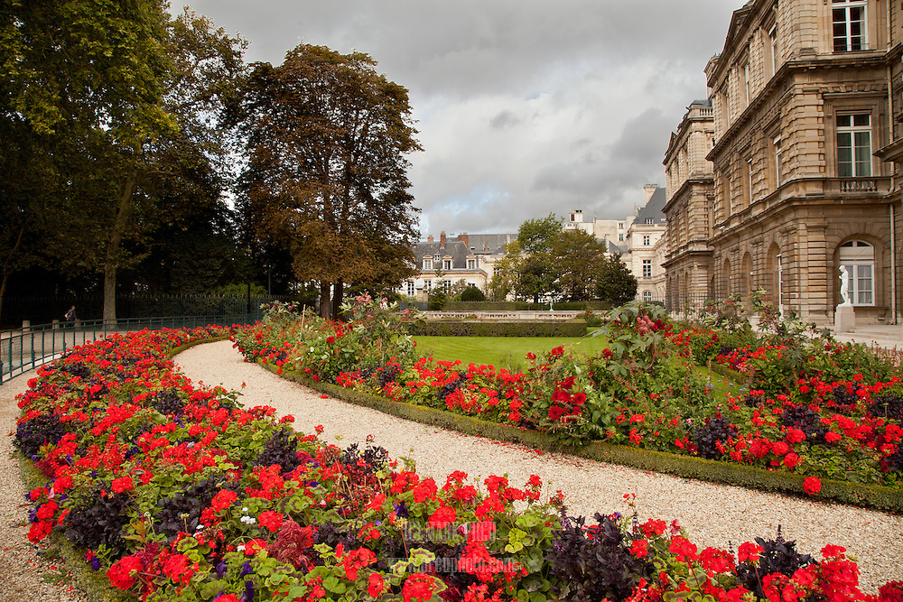 A gravel path, lined with brilliant geraniums, surrounds a corner of the Luxembourg Palace in Paris.