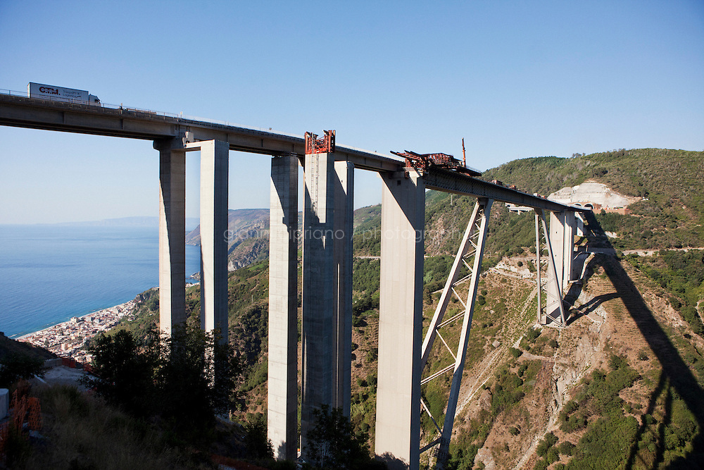 Bagnara, Italy - 18 July, 2012:  A truck passes by the Sfalassà bridge on 18 July, 2012, in Bagnara, Italy. The Autostrada A3 Salerno-Reggio Calabria is a motorway in the south of Italy, which runs from Salerno to Reggio Calabria via Salerno. Due to its notorious poor conditions of maintenance, and its difficult route, the motorway has been often taken as a symbol of the backwardness and economical problems of southern Italy. bridge on 18 July, 2012, in Bagnara, Italy. The Autostrada A3 Salerno-Reggio Calabria is a motorway in the south of Italy, which runs from Salerno to Reggio Calabria via Salerno. Due to its notorious poor conditions of maintenance, and its difficult route, the motorway has been often taken as a symbol of the backwardness and economical problems of southern Italy.