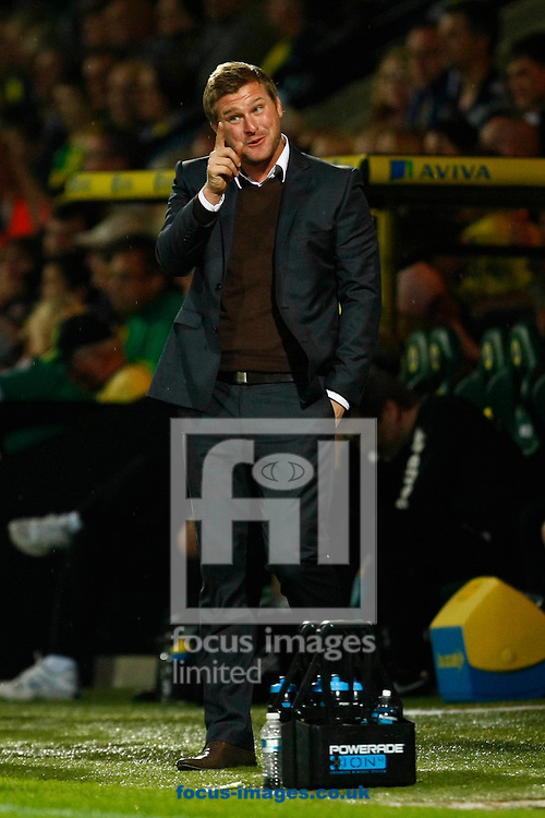 MK Dons Manager Karl Robinson looks happy after his sides 2nd goal during the Carling Cup 2nd Round match at Carrow Road Stadium, Norwich, Norfolk...Picture by Paul Chesterton/Focus Images Ltd.  07904 640267.23/8/11
