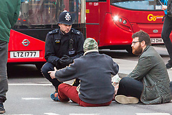 PICTURED: A police officer talks with anti pollution protesters as they sit in the road blocking traffic at Marble Arch. Demonstrators from the anti-pollution group Stop Killing Londoners cause traffic chaos for London commuters as they conduct a series of short roadblocks at Marble Arch stopping cars and buses from entering Oxford Street and Park Lane. Irate motorists accused them of creating more pollution than they were stopping, whilst the group said their objectives were long term. A leaflet handed out to motorists says the government is not doing enough to tackle the crisis costing 'taxpayers and the NHS £billions [sic] a year'. PLACE, January 29 2018. © Paul Davey