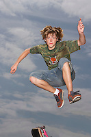 Teenage boy (16-17) jumping on skateboard on street low angle view