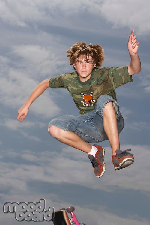 Teenage boy (16-17) jumping on skateboard on street low angle view