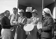 """Irish Distillers Grand National at Fairyhouse.  (M66)..1979..16.04.1979..04.16.1979..16th April 1979..The Irish Distillers Grand National was run today at Fairyhouse Racecourse, Co Meath.The race over 3.5miles is valued at £20,000. the winning trainer will also receive the Tom Dreaper,Perpetual Trophy which will be presented by Mrs Betty Dreaper..Picture of winning owner and rider of """"Tied Cottage"""", Mr Anthony Robinson accepting his trophy from Mrs Michael Kennedy,also pictured are Mr Richard Burrows,MD,Irish Distillers Ltd, Mrs Dreaper and Mrs Joan Moore, wife of the winning trainer,Mr D L Moore."""