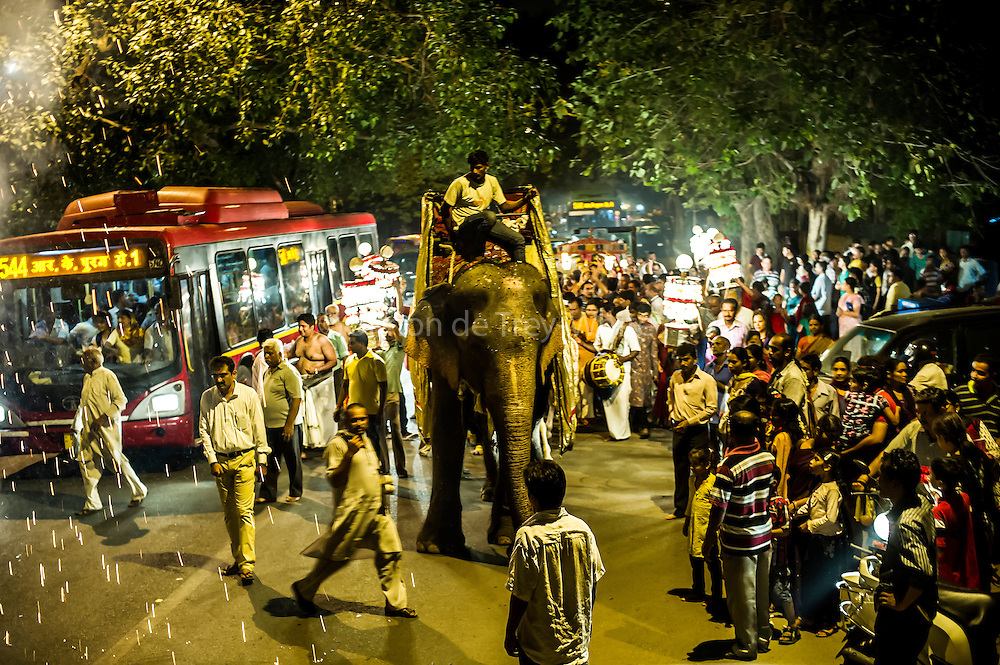 29th August 2014, Sarojini Nagar, New Delhi, India. Female elephant Gulabo ridden by her handler leads a  Sidhi Budhi Vinayaka procession through the streets as a firework goes off, near the Sree Vinayaka Mandir in New Delhi, India on the 29th August 2014 as part of the Ganesh Chaturthi religious festival<br />