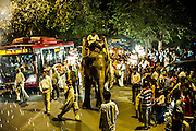 29th August 2014, Sarojini Nagar, New Delhi, India. Female elephant Gulabo ridden by her handler leads a  Sidhi Budhi Vinayaka procession through the streets as a firework goes off, near the Sree Vinayaka Mandir in New Delhi, India on the 29th August 2014 as part of the Ganesh Chaturthi religious festival<br /> <br /> Ganesh Chaturthi is the Hindu festival celebrated in honour of the god Ganesha, the elephant-headed, remover of obstacles and the god of beginnings and wisdom.<br /> <br /> Elephant handlers (Mahouts) eke out a living in makeshift camps on the banks of the Yamuna River in New Delhi. They survive on a small retainer paid by the elephant owners and by giving rides to passers by. The owners keep all the money from hiring the animals out for religious festivals, events and weddings, they also are involved in the illegal trade of captive elephants.The living conditions and treatment of elephants kept in cities in North India is extremely harsh, the handlers use the banned 'ankush' or bullhook to control the animals through daily beatings, the animals have no proper shelters are forced to walk on burning hot tarmac and stand for hours with their feet chained together. <br /> <br /> PHOTOGRAPH BY AND COPYRIGHT OF SIMON DE TREY-WHITE<br /> + 91 98103 99809<br /> email: simon@simondetreywhite.com photographer in delhi