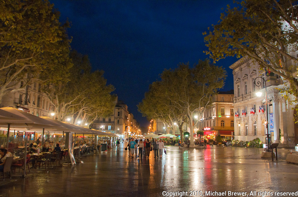 People walking round a plaza in Avignon on a rainy night in September in France.