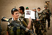 An Afghan National Army soldier holds a photo of a wanted man during a joint patrol with U.S. soldiers in the Arghandab Valley of Kandahar Province.