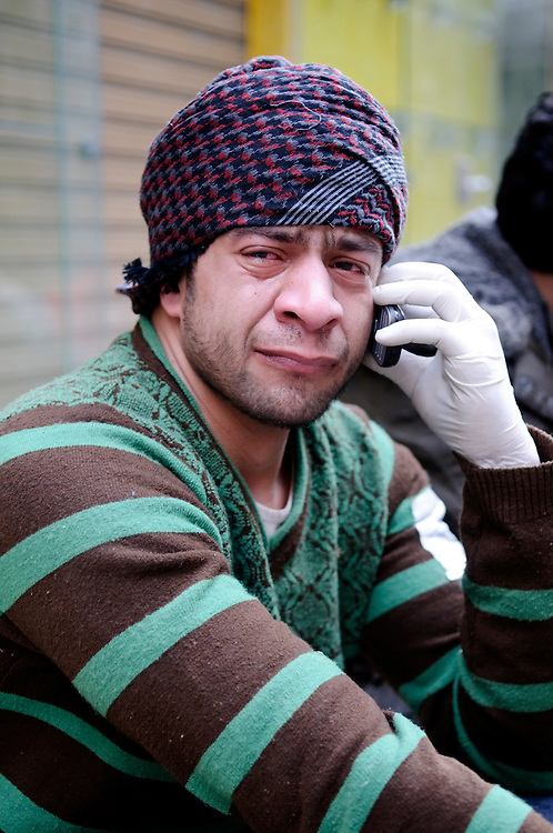 A man pauses briefly for a phone call while treating a flood of protestors in Tahrir Square who had been injured by pro-government counter-demonstators. (Cairo Egypt - February 2, 2011)