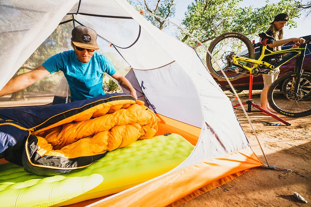 Dane Cronin sets up camp while Jeremy Hottinger wrenches on his bike, Virgin, Utah.