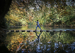 © Licensed to London News Pictures. 27/10/2015. Dorking, UK. A boy crosses the stepping stones over The River Mole near Box Hill . Photo credit: Peter Macdiarmid/LNP