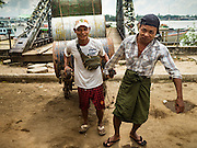 03 NOVEMBER 2015 - YANGON, MYANMAR: Men move empty oil barrels on the Yangon docks.    PHOTO BY JACK KURTZ