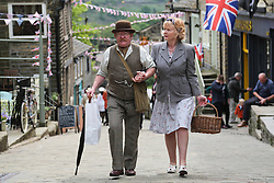 © Licensed to London News Pictures. 13/05/2016. Haworth, UK. A man and woman in 1940s costume walk up a bunting draped street during the annual 1940's weekend in Haworth, West Yorkshire.  Photo credit : Ian Hinchliffe/LNP