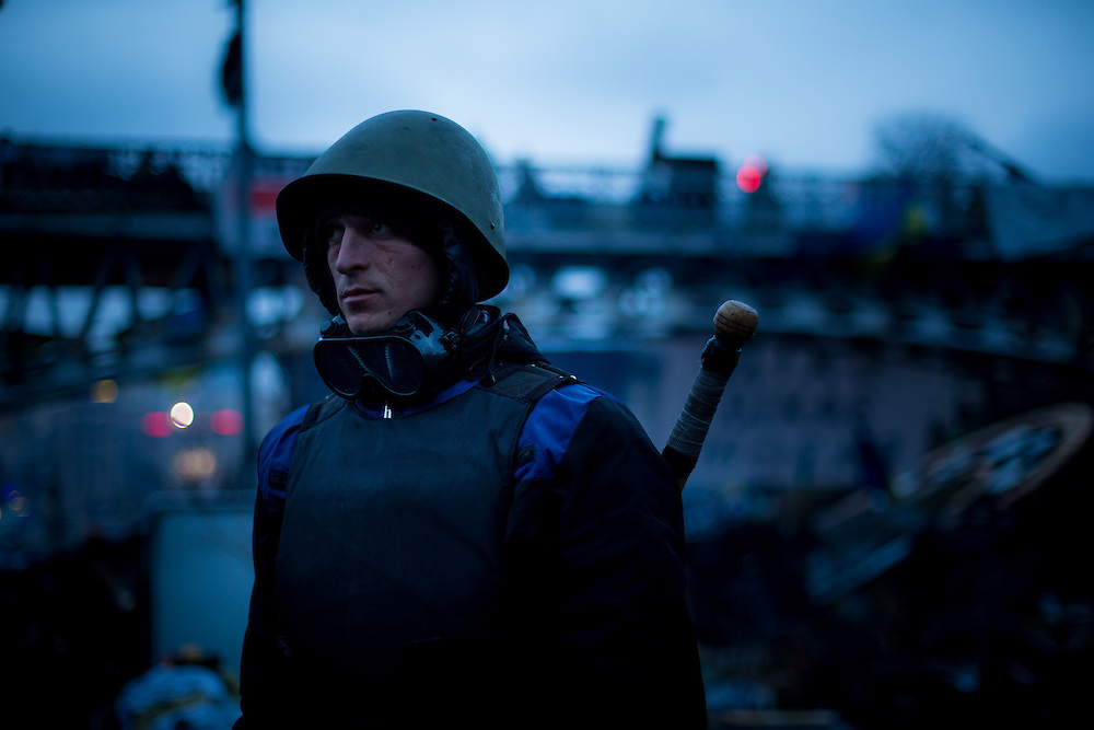 A fighter of Maïdan wearing an helmet, a stick and a bulletproof vest, guards one of the entrance of the Independance Square, in Kiev.