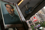 Chairman Mao Tse Tung looks out from a poster in a food shop, whilst outside the shop Colonel Sanders, the icon for the Kentucky Fried Chicken fast food empire, looks down on a Guangzhou street. Guangzhou is believed to be the city where the SARS virus originated.