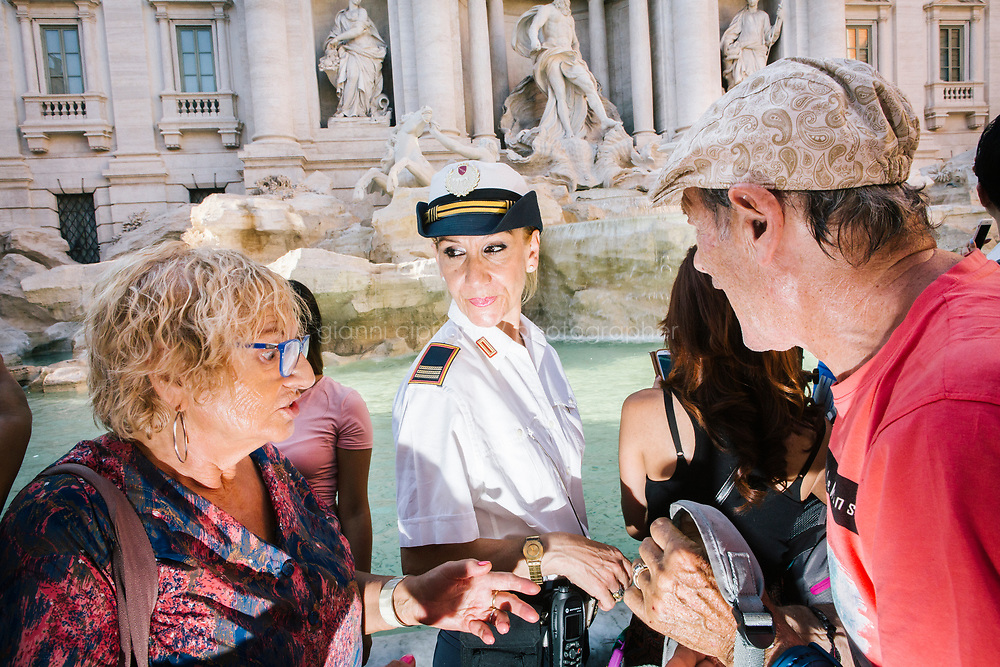 ROME, ITALY - 20 JUNE 2017: A Roman policewoman, entrusted to protect the Fountain of Trevi, is seen here with tourists by the fountain in Rome, Italy, on June 20th 2017.<br /> <br /> The warm weather has brought a menacing whiff of tourists behaving badly in Rome. On April 12, a man went skinny-dipping in the Trevi fountain resulting in a viral web video and a 500 euro fine.<br /> <br /> Virginia Raggi, the mayor of Rome and a national figurehead of the anti-establishment Five Star Movement,  issued an ordinance involving harsher fines for eating, drinking or sitting on the fountains, for washing animals or clothes in the fountain water or for throwing anything other than coins into the water of the Trevi Fountain, Bernini&rsquo;s Four Fountains and 35 other city fountains of artistic or historic significance around the city.  &ldquo;It is unacceptable that someone use them to go swimming or clean themselves, it&rsquo;s an historic patrimony that we must safeguard,&rdquo; Ms. Raggi said.