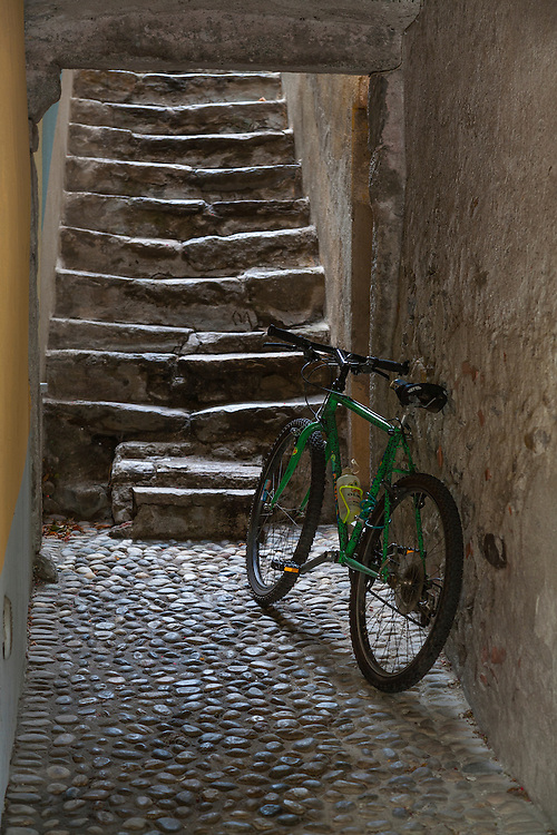Green bicycle leans against old plaster wall at base of ancient worn stone steps and cobblestones