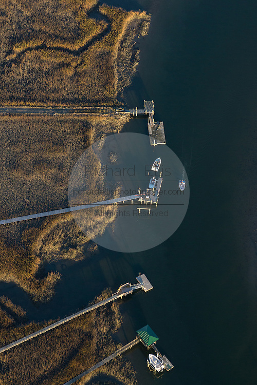 Aerial view of a boat passing docks along Shem Creek in Mt Pleasant, SC