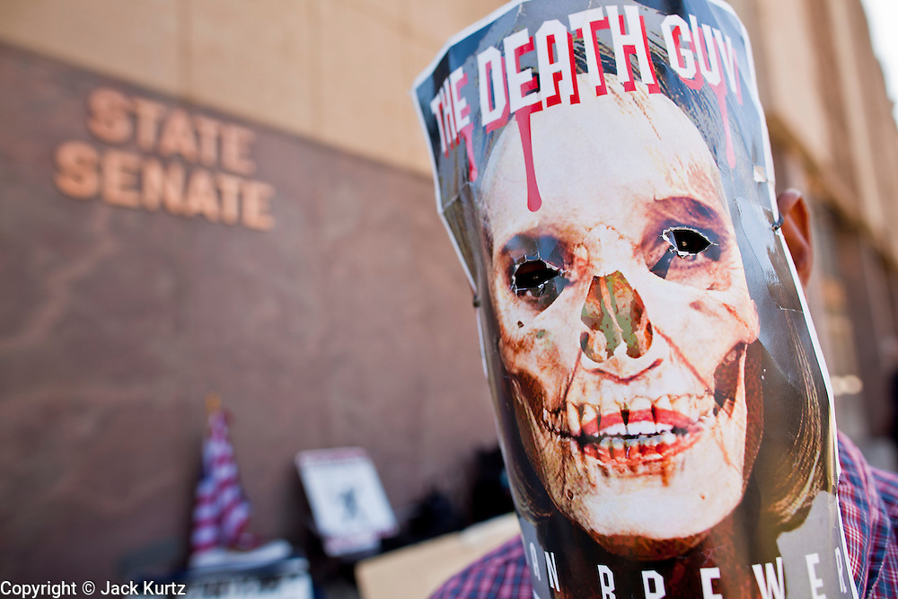 15 APRIL 2011 - PHOENIX, AZ: An immigrants' supporter wears a mask as a protest against Arizona Gov. Jan Brewer and Republicans in the state legislature during a protest against the Tea Party in Phoenix Friday. About 500 supporters of the Tea Party movement rallied Friday at the Arizona State Capitol to mark tax day. They protested high taxes, the federal deficit, the debt limit and immigration policy. About 50 pro-immigrant protesters held a counter rally at the capitol. At least one person was arrested, and others led away by police after several shouting matches between Tea Party supporters and the immigrants rights protesters broke out.     PHOTO BY JACK KURTZ