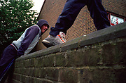 Two teenage boys climbing over a garden wall in a housing estate Lambeth Walk South London c.2000