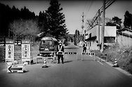 Police checkpoint at an western entry point the 20 km (12.4 miles) nuclear no-entry zone.  Kawauichi, Fukushima Prefecture, Japan.  As of midnight 21 April 2011, the Japanese government declared the no-entry zone off-limits under the Disaster Countermeasures Basic Law which gives the police the power to detain anyone entering the zone for up to 30 days and imposes a fine of up 100,000 JPY (US$1,200).