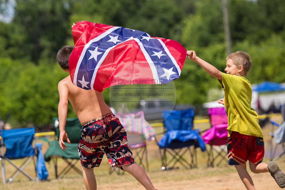 Young boys run around with a confederate flag during the 2015 National Red Neck Championships May 2, 2015 in Augusta, Georgia. Hundreds of people joined in a day of country sport and activities.