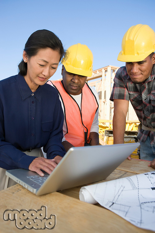 Architect and two construction workers using laptop