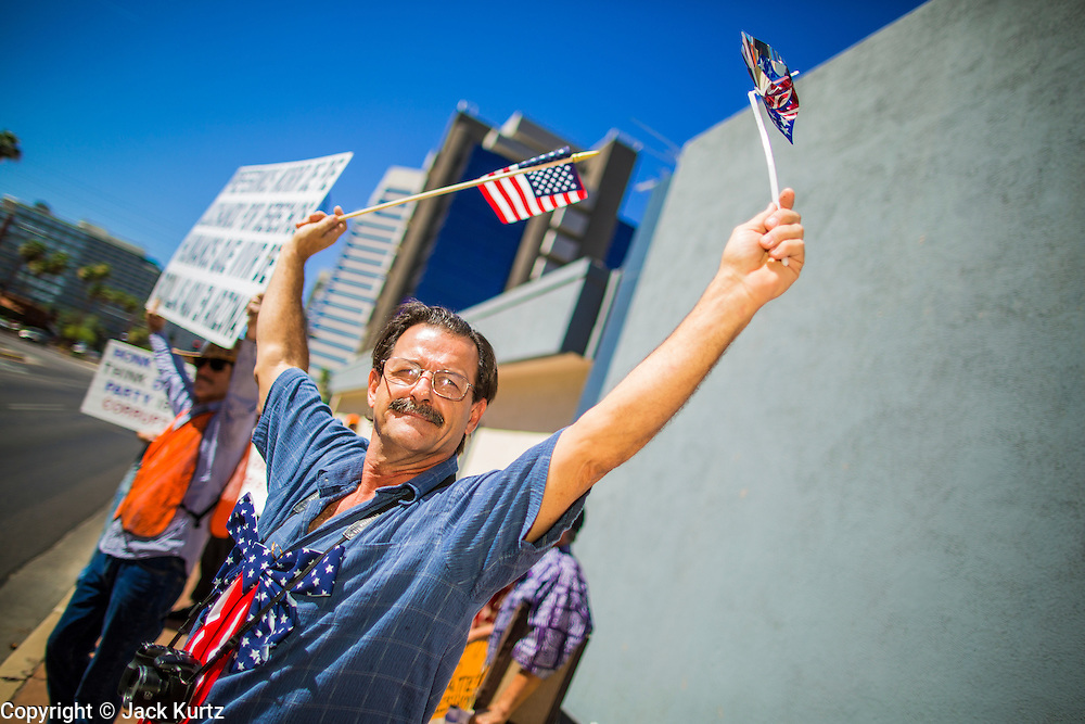 08 JUNE 2012 - PHOENIX, AZ:  NICK THOMAS, from Mesa, AZ, pickets the Arizona Democratic party headquarters. About 30 members of the Arizona Democratic Party picketed party headquarters Friday to show their unhappiness with party leadership. They claim the party, or party endorsed candidates, is accepting money from the American Legislative Exchange Council (ALEC) and is not properly supporting Democratic candidates not endorsed by the party, even during the primaries.           PHOTO BY JACK KURTZ