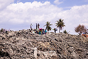 Villagers are seen walking on a mount of dry mud that is the remains of Petobo, a village that was swallowed by a sinkhole or Liquefaction triggered by an earthquake of 7.5 earthquake magnitude that hit off the coast of Donggala, Palu Sulawesi Central, Indonesia on Sept. 28th.  About 1,700 houses were buried by mud.