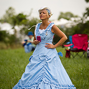 Mimi Chambers, of Birmingham, AL, watches the reenactment of Pickett's Charge from a distance in her period dress, during the Sesquicentennial Anniversary of the Battle of Gettysburg, Pennsylvania on Sunday, June 30, 2013.  She and her friend decided to participate as a civilian reenactor for the first time this year.  John Boal photography