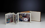 An accordion book bound into hard covers with photographs