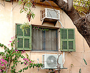 Old and new air-conditioning unites arranged around a window