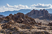 Heart Arch punctuates the abstract landscape of BLM Alabama Hills Recreation Area, in the Owens Valley, west of Lone Pine in Inyo County, California, USA. The Inyo Mountains rise in the background (in the east). The Alabama Hills are a popular filming location for television and movie productions (such as Gunga Din, Gladiator, Iron Man,  Transformers: Revenge of the Fallen), especially Westerns (Tom Mix films, Hopalong Cassidy films, The Gene Autry Show, The Lone Ranger, Bonanza, How the West Was Won, and Joe Kidd). Two main types of rock are exposed at Alabama Hills: 1) orange, drab weathered metamorphosed volcanic rock 150-200 million years old; and 2) 82- to 85-million-year-old biotite monzogranite which weathers to potato-shaped large boulders.