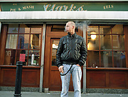 Alexander McQueen smoking a cigarette on the pavement in front of Clarks pie shop.
