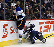 St. Louis Blues' Jordan Leopold (33) plays the puck as Winnipeg Jets' Jacob Trouba (8) appears to catch an edge and launch himself into the boards during the second period of play at MTS Centre in Winnipeg, Friday, October 18, 2013.