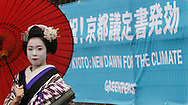 """'Kosen"""", a 20 year old Maiko girl from Kyoto, stands in front of a sign marking the implementation of the Kyoto Protocol Agreement. The Agreement comes into force on Febuary 16th 2005, and was marked by events and conferences in Kyoto involving Greenpeace and Solar Generation, a youth group environmental NGO, Japan."""