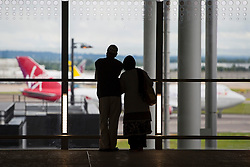 © Licensed to London News Pictures. 04/06/2014. LONDON, UK. A couple watching landing planes as London Heathrow's new Terminal 2 opens to passengers on Wednesday, 4 June 2014. The new terminal has 60 check-in gates and 66 self-check-in kiosks, 29 security lanes, 33 shops and 17 restaurants. On the first day of operation, airport welcomed 34 United flights for the US. Photo credit : Tolga Akmen/LNP